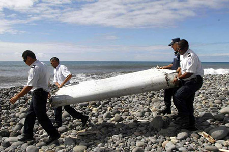 Officers carrying pieces of debris from an unidentified aircraft on the island of La Reunion on July 29, 2015. PHOTO: EPA