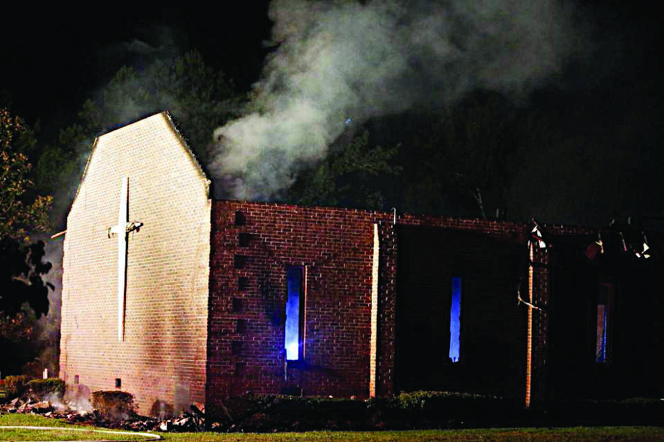 Smoke rises from Mount Zion African Methodist Episcopal church late Tuesday, June 30, 2015, in Greeleyville, S.C., which caught fire Tuesday. The African-American church that was burned down by the Ku Klux Klan in 1995 caught fire again Tuesday night. (Veasey Conway/The Morning News via AP)