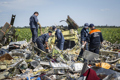 Ukrainian rescue servicemen inspect part of the wreckage of Malaysia Airlines flight MH17 on July 20, 2014 in Rassipnoye, Ukraine. Malaysia Airlines flight MH17 was travelling from Amsterdam to Kuala Lumpur when it crashed killing all 298 on board including 80 children. The aircraft was allegedly shot down by a missile and investigations continue over the perpetrators of the attack.  (Photo by Rob Stothard/Getty Images)
