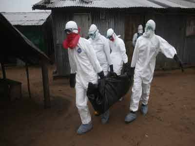 A burial team wearing protective clothing retrieves the body of a 60-year-old who died from Ebola. Photo credit cnn