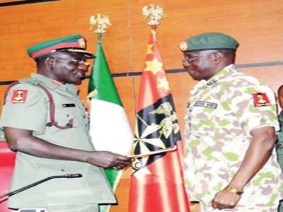 Chief of Army Staff and outgoing head of the Multi-National Joint Task Force (MNJTF), Major-General Tukur Buratai (left) with the new head of the MNJTF, Major-General Iliya Abbah, during a handover ceremony in Abuja yesterday.