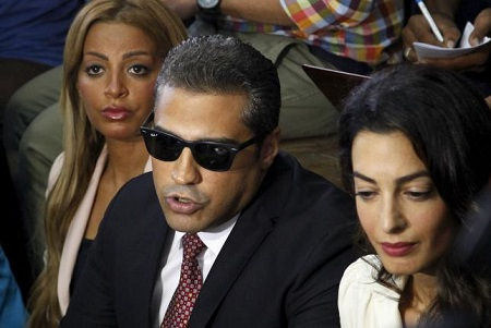 Al Jazeera television journalist Mohamed Fahmy, C, talks to the media, with his wife, Marwa Omara, L, and lawyer Amal Clooney (R), before hearing the verdict at a court in Cairo, Egypt, August 29, 2015. REUTERS/Asmaa Waguih