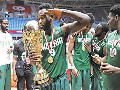 D'Tigers' Chamberlain Oguchi celebrates with the AfroBasket trophy after Nigeria's 74-65 defeat of Angola in the final of the competition in Rades, Tunisia… on Sunday. PHOTO: FIBA.COM