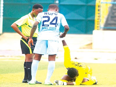 A Nigerian referee attending to an injured player during an Enyimba versus Nasarawa United game. The NFF says it wants to sanitise officiating in the Glo Premier League.