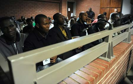A picture taken on March 8, 2013 shows some of the South African police officers on trial in Benoni court over the death of Mido Macia, a Mozambican taxi driver who died in custody after being dragged behind a police van PHOTO: © Pool/AFP/File Werner Beuke
