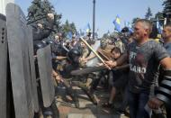 Ukrainian protesters clash with police after a vote to give greater powers to the east, outside the Parliament, Kiev, Ukraine, Monday, Aug. 31, 2015. The Ukrainian parliament has given preliminary approval to a controversial constitutional amendment that would provide greater powers to separatist regions in the east. Hundreds of people gathered in front of the parliament to protest against the amendment. (AP Photo/Efrem Lukatsky)