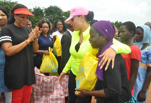Mrs Iara Oshiomhole, wife of Edo State Governor, presents some items to Internally Displaced Persons at the IDP Camp in Uhogua, Benin City Edo State, during the Governor's wife's visit to the camp, on Friday.