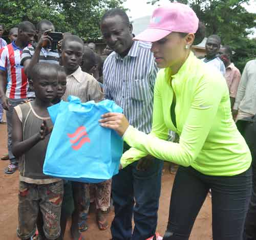 Mrs Iara Oshiomhole, wife of Edo State Governor, presents some items to Internally Displaced Persons at the IDP Camp in Uhogua, Benin City Edo State, during the Governor's wife's visit to the camp, on Friday