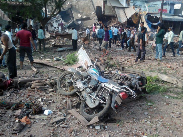 People gather around the site of an explosion at a restaurant in Jhabua district , India. PHOTO: tribune