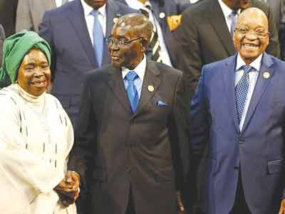 Chairperson of the African Union (AU) Commission Nkosazana Dlamini-Zuma (left) being greeted by Zimbabwe and African Union President Robert Mugabe, with South Africa's President Jacob Zuma at a recent summit of the continent's leaders in Johannesburg