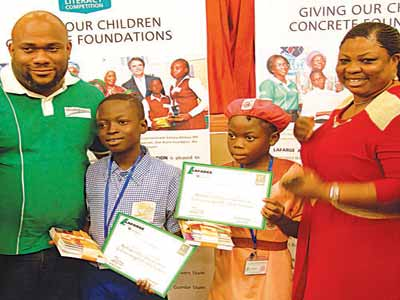 Members of the Lagos State Team, and winners of the South West Regional Leg of the Lafarge, Ovie-Brume Literacy Competition, Ageni Joseph of Ifeoluwa Primary School Agege, (second, left) and Hameedah Amos of St. Agnes Primary School. They are flanked by member, Lafarge Friends Of Community, Mr. Kenneth Ohiorenoya, and an official of the Lagos State Universal Basic Education Board (UBEB), Mrs. Bunmi Oteju, after the event, which held in Abeokuta, Ogun State...recent