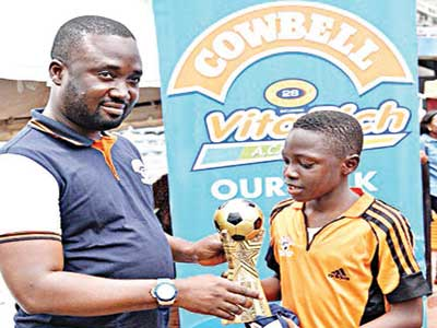 Category Manager – Diary, Promasidor Nigeria Limited, Abiodun Ayodeji, handling over the trophy to the captain of the victorious Team River Niger at the end of Cowbell Football Academy Summer Camp 2015 held at the National Stadium, Surulere, Lagos.