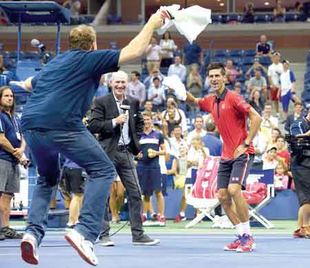 Novak Djokovic (right) dances on the court with a fan after defeating Andreas Haider-Maurer during their US Open 2015 second round match…yesterday. PHOTO: AFP.