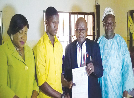 Executive Secretary, Ejigbo LCDA, Barrister Jaiye Alabi (second right) presenting GCE photocard to Adebesin Adeniyi (second left) during presentation of free GCE to 50 beneficiaries at the council secretariat recently. With them are the Council Manager, Nurudeen Shobajo (right) and Secretary to the council, Mrs.Abimbola Ike-Nicholas