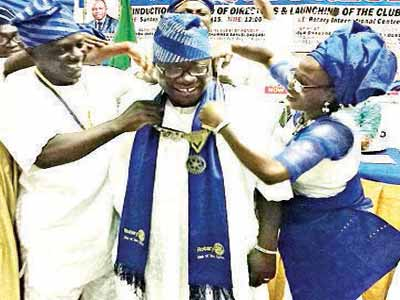 Rotarian Jaiye Alabi (middle) being decorated as the 12th President of Ewutuntun Rotary Club by his wife and the immediate past president of the club, Rotarian Yomi Owolabi (left).