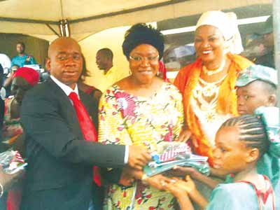 Executive Secretary of Lagos Island Local Government, Adetoyese Olusi (left) presenting some of the school kits to the pupils on Monday.