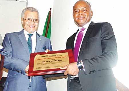 Majekodunmi presenting an award to the Managing Director of Lagos State Waste Management Agency (LAWMA), Mr. Ola Oresanya