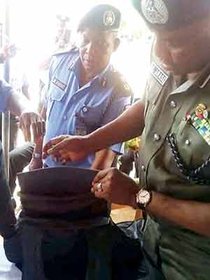 IGP Arase (left) inspecting the bulletproof vest and Inspector Hosea (right) being decorated.
