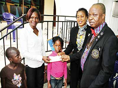 District Governor, Ogudu-GRA Rotary club, Rotarian Bola Onabadejo and the Club's President, Rotarian Fidel Ogwuazor presenting cheque for sponsorship of the two children at the Little Saints Orphanage to their representatives while the children look on.
