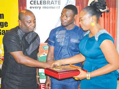 Nollywood Actress, Alexa Ehi (right) presenting an award of excellence to actor/ and comedianBasorge Tariah (left) while IDL Marketing Manager looks on