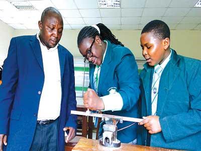 Basic Technology teacher, City of Knowledge Academy (CKA), Ijebu Ode, Tajudeen Ayantola (left), students of the school, Sanaa Akindele and Michael Momoh, learning metal work in the school's technology workshop