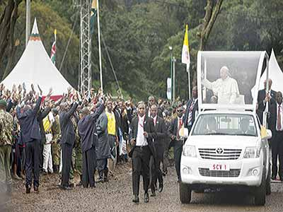 Pope Francis waving to the crowd as he arrived to hold a Mass at the campus of the University of Nairobi, Kenya yesterday. Francis met with a small group of Kenya's faith leaders before celebrating his first public Mass on the continent, a joyful, rain-soaked celebration attended by tens of thousands of faithful, including Kenya's president. PHOTO: AP PHOTO/BEN CURTIS
