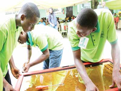 Students of Doregos Private Academy, Ipaja, Lagos, Udekwe Joseph, Eyafe Ese and Oma Victor, constructing aluminium window during the Young Entrepreneur Fair of the school.