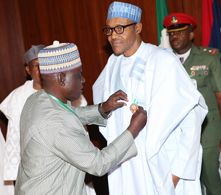 PRESIDENT BUHARI LAUCH 2016 ARMED FORCES EMBLEM; 0A. L-R; Minister of Defence, Muhammad Mansur Dan-Ali, President Muhammadu Buhari being decorated by the Sec Gen Nigerian Legion, Capt JA Adole (Rtd) during the launching of Emblem year 2016 armed forces remembrance day celebration held at the Council Chamber State House in Abuja. PHOTO; SUNDAY AGHAEZE. NOV 16 2015.