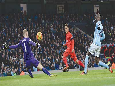 Liverpool's Brazilian midfielder Roberto Firmino (middle) takes an unsuccessful shot on goal during the Premiership match against Manchester City at The Etihad stadium on Saturday.    PHOTO: AFP