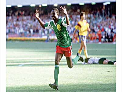 Roger Milla wheels away in delight after beating Rene Higuita to score Cameroun's second goal against Colombia at the Italy '90 World Cup. PHOTO: FIFA.COM