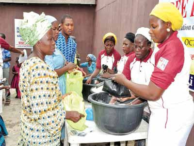 Officials of Foursquare Church, Ojodu Abiodun, distributing food items to residents during the free food day service organised by the Church.