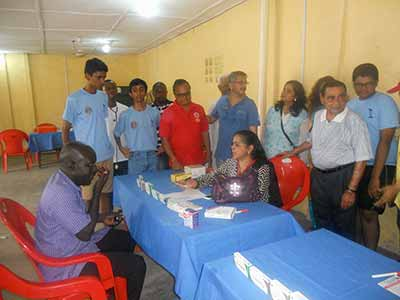Rotarian N.G. Patel (3rd right), Mrs. Chetana Piyara, Managing Director, JMD Pharmalinks, Rotarian Shrinivas Joshi, Chairman, Service Projects, Suresh Nair, Coordinator, Service Project, Rotarian Jaya Shankar Nalode and others as Dr. Latha Ravikumar (sitting) was attending to a beneficiary, Safiyanu Osagede at the event