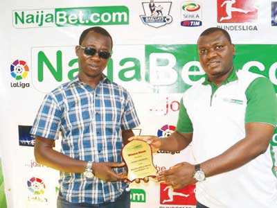 Head of Marketing, Naija.Com, Saheed Gbajabiamila (left), presenting a plaque to Ayinde Emmanuel, who won N1.4 million from the betting company…at the weekend