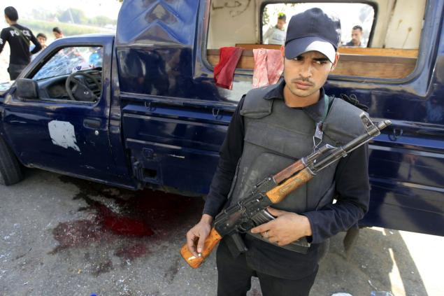 An armed Egyptian security guard stands at the site of an attack on four policemen Friday in Giza, near Cairo, Egypt. Photo:  nydailynews