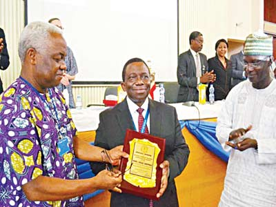 President, University French Teachers' Association of Nigeria (UFTAN), Professor Tunde Fatunde (left), presenting an award to the immediate past vice chancellor of University of Ibadan, and Health Minister, Professor Isaac Adewale, while Head of Department, Department of European Studies, University of Ibadan, Professor Babatunde Ayeleru looks on.