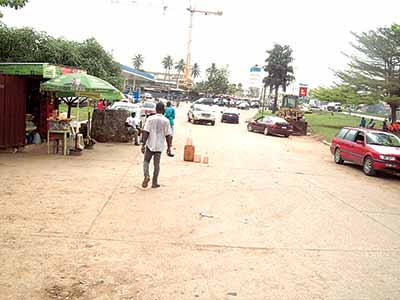Black market...Gallons of petrol (foreground) for sale near a filling station along Airport road, Lagos