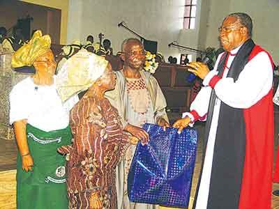 Bishop Oluranti Odubogun (right), Diocesan Chancellor, Professor Gabriel Olawoyin, his wife, Mrs. Olawoyin and Mrs. Folashade Odubogun as Odubogun presents a gift to Olawoyin, during the anniversary celebration.              PHOTO:  ISAAC TAIWO