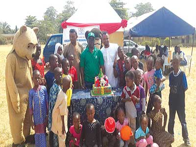 Founder of Kokumo Memorial Foundation, Bashorun Muyiwa Oladipo, flanked by children during the empowerment programme.