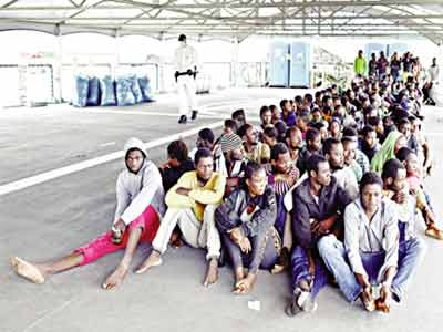 Over 140 migrants and refugees from Nigeria, Ghana, Senegal and Sierra Leone who were transported by the German navy frigate Werra as part of the European external action service EU Navfor Med, wait to disembark at the Augusta harbour in eastern Italy...recently                                     CREDIT: GOOGLE