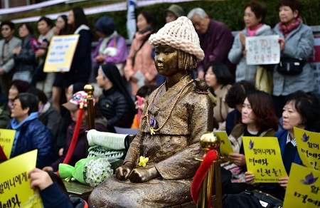 "Protestors in Seoul sit next to a statue of a South Korean teenage girl in traditional costume called the ""peace monument"" for women used as sex slaves by Japanese soldiers during World War II (AFP Photo/Jung Yeon-Je)"