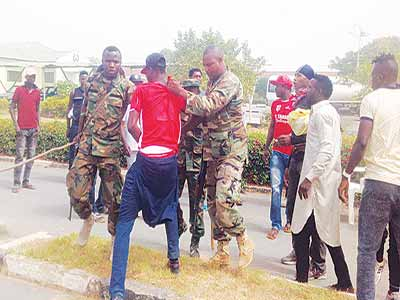 Taraba FC players being manhandled by soldiers during protest over none payment of their salaries and match bonuses…yesterday in Jalingo. Photo: Charles Akpeji