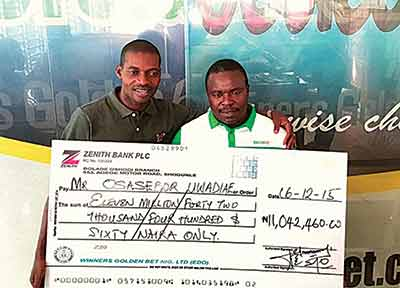 General Manager of Winners Golden Bet, Mr. Ayowole Sajimi, presenting a cheque of over N11 million to Mr. Osaseboh Uwadiae, at the company's head office in Lagos
