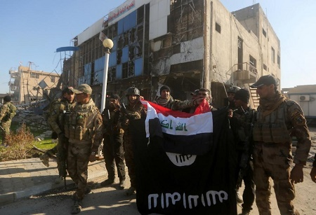 Iraqi security forces place the national flag above the Islamic State group flag on December 28, 2015 in front of the Anbar police headquarters after they recaptured Ramadi, the capital of Anbar province (AFP Photo/Ahmad Al-Rubaye)