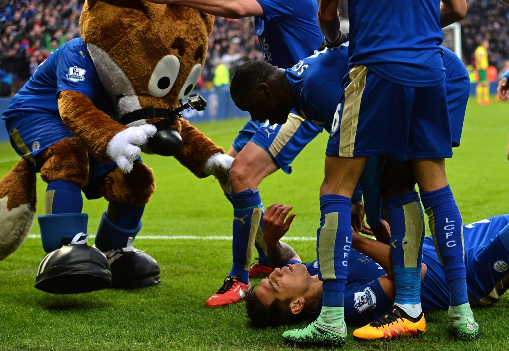 Leicester City's Argentinian striker Leonardo Ulloa on the floor, celebrates with Leicester City's players and mascot after scoring the opening goal of the English Premier League football match between Leicester City and Norwich City at King Power Stadium in Leicester, central England on February 27, 2016. Leicester won the game 1-0. / AFP / Paul ELLIS / RESTRICTED TO EDITORIAL USE. No use with unauthorized audio, video, data, fixture lists, club/league logos or 'live' services. Online in-match use limited to 75 images, no video emulation. No use in betting, games or single club/league/player publications.  /