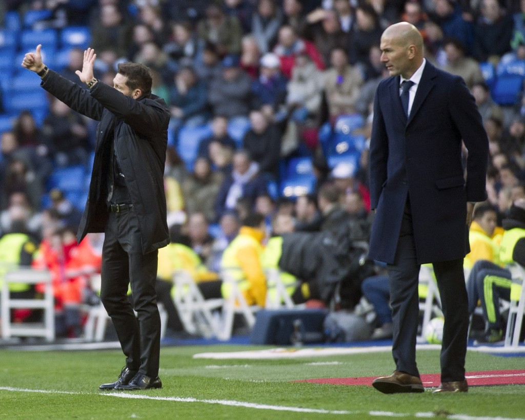 Atletico Madrid's Argentinian coach Diego Simeone (L) gestures next to Real Madrid's French coach Zinedine Zidane during the Spanish league football match Real Madrid CF vs Club Atletico de Madrid at the Santiago Bernabeu stadium in Madrid on February 27, 2016. / AFP / CURTO DE LA TORRE