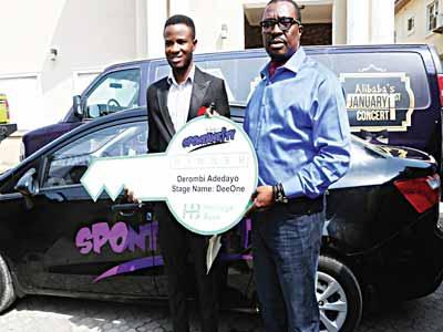 Comedian Alibaba presents star prize to Spontaneity winner Aderombi Adebayo.