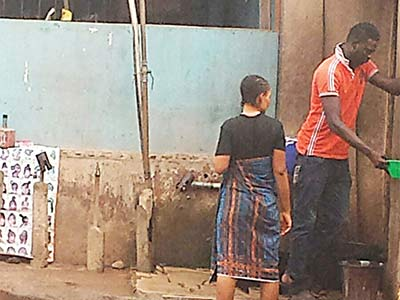 Residents fetching water from a tap in the neigbourhood PHOTO: AYOBAMI ADEOYE