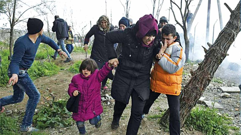 A woman holding her children as they run away after Macedonian police fired tear gas... yesterday PHOTO: GIANNIS PAPANIKOS/AP