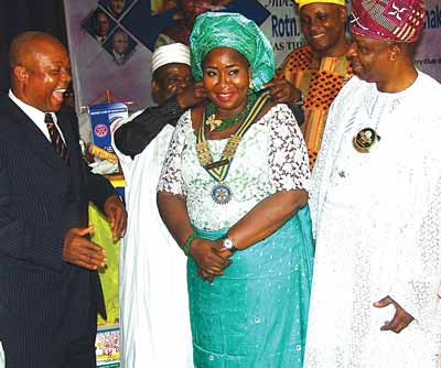 District Governor, Rotary International, District 9110 comprising Lagos and Ogun states, Otunba Bola Onabadejo (right), Immediate Past President, Rotary Club of Isolo, Rotarian Adegoke Adeoye, and r Abdullahi Asen Enakhume (left) and immediate past President, Hakeem Ibrahim decorating the in-coming President, Zainab Grace Enakhume.