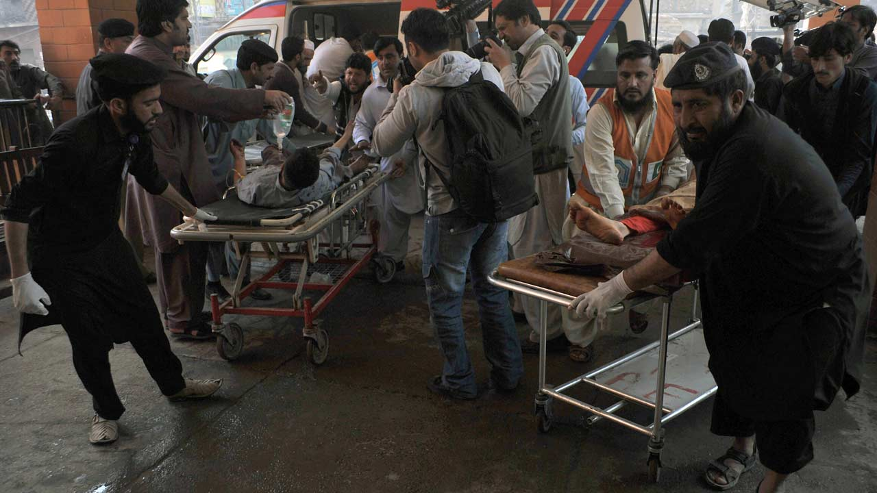 Pakistani security personnel and volunteers move victims injured in a suicide bombing to a hospital in Peshawar on March 7, 2016, after an attack on a court complex in the town of Shabqadar. A suicide bomber blew himself up at a court complex in northwest Pakistan, killing at least eight people and injuring 21, police said. HASHAM AHMED / AFP